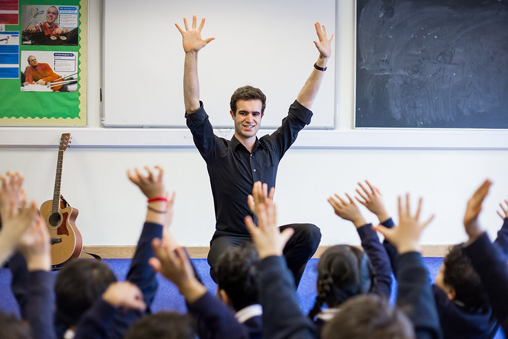 Male sitting in classroom with primary pupils all with hands in the air, brown guitar, chalkboard, and colourful display board.