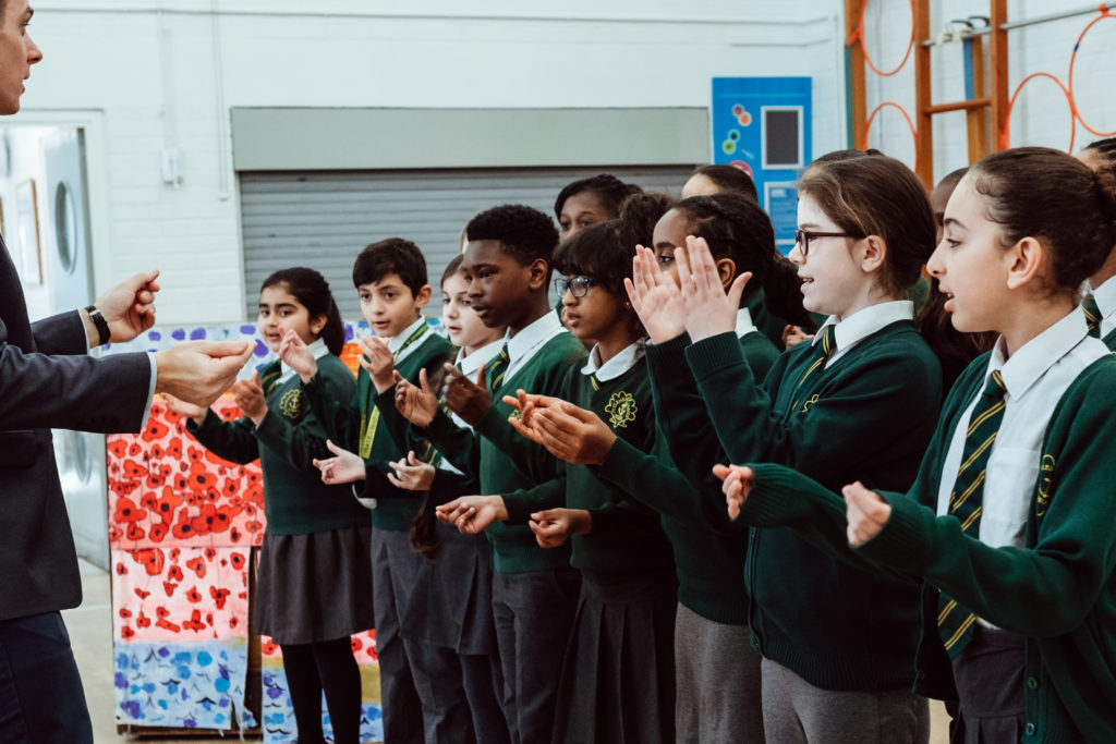 Male in front of thirteen primary KS2 pupils, using hand actions for a song, in school music hall.