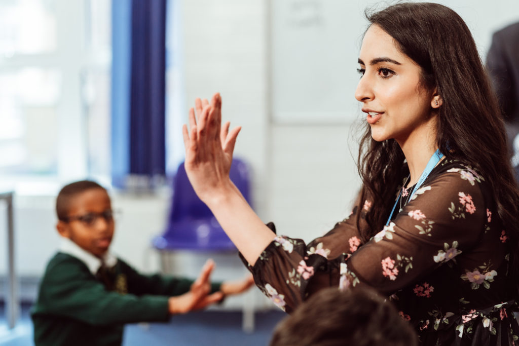 Female in music classroom, hands clapping in front of her and a KS1 primary pupil copying.