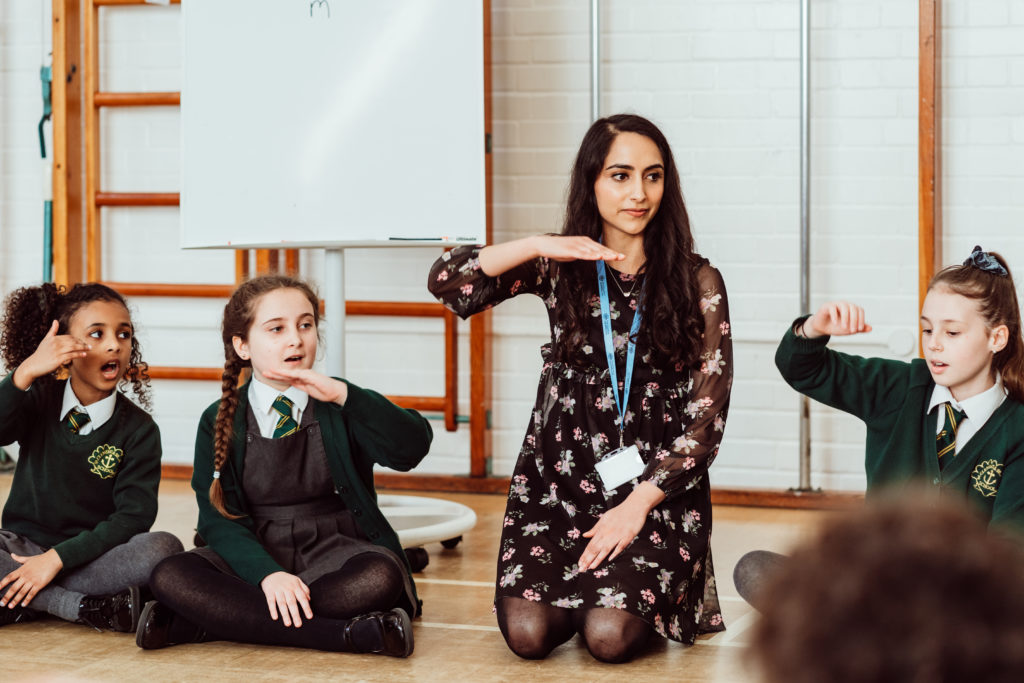 Female sitting on the floor in a circle in school hall, four primary pupils are singing using their hands.