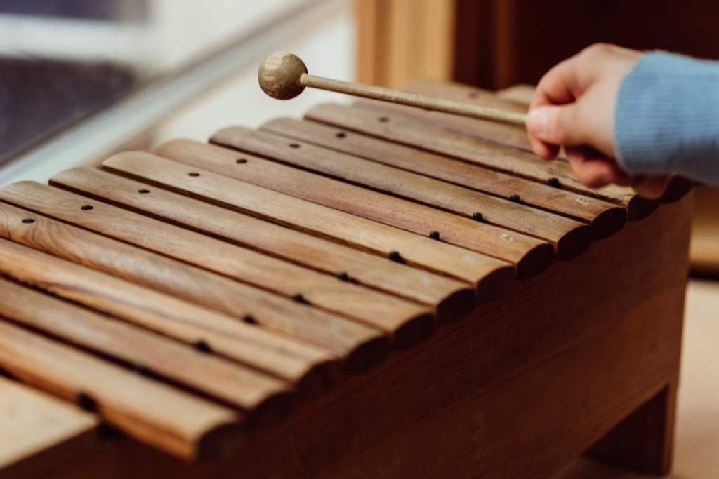 Close up-Hand holding brown wooden beater above brown wooden glockenspiel