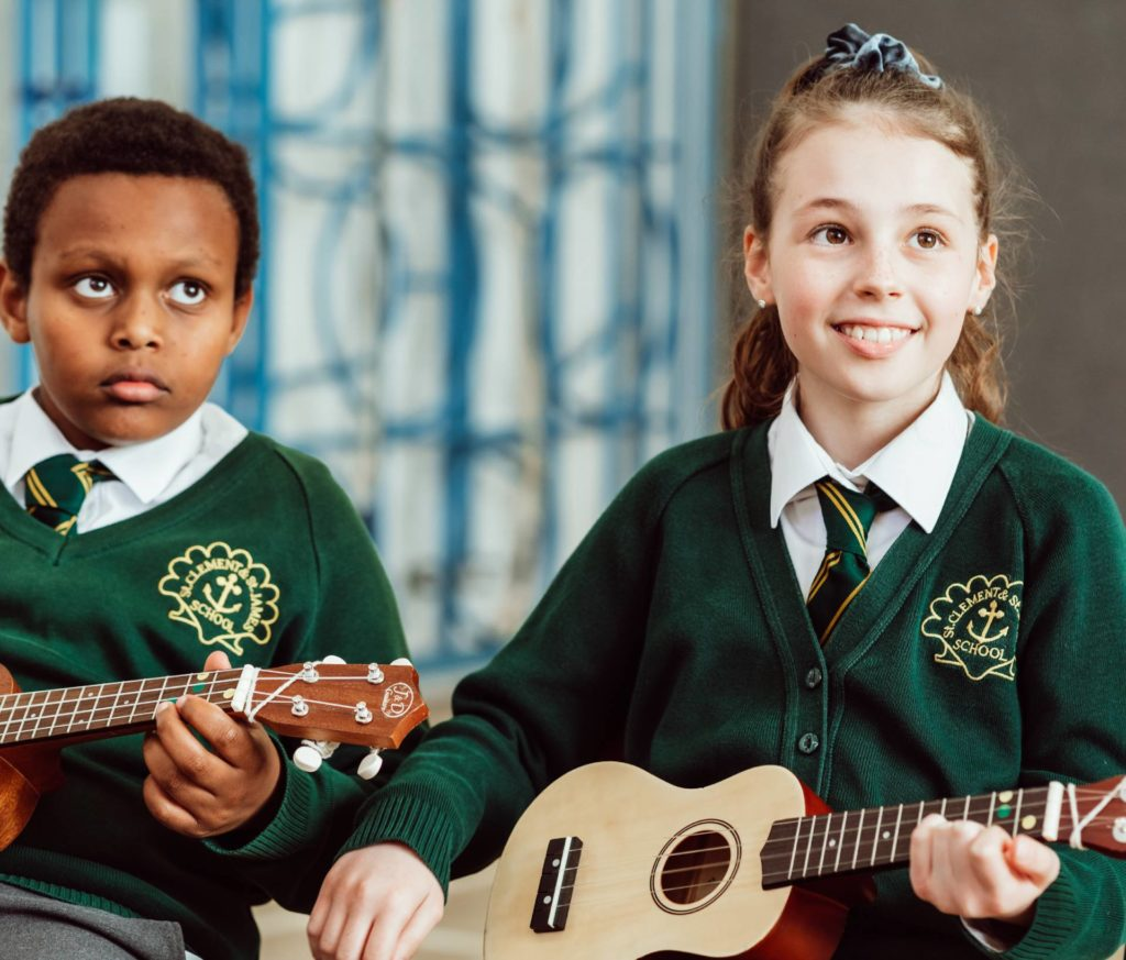 Two KS2 primary pupils, holding Ukuleles, sitting in school hall, on chairs, both pupils holding brown Ukuleles, smiling.