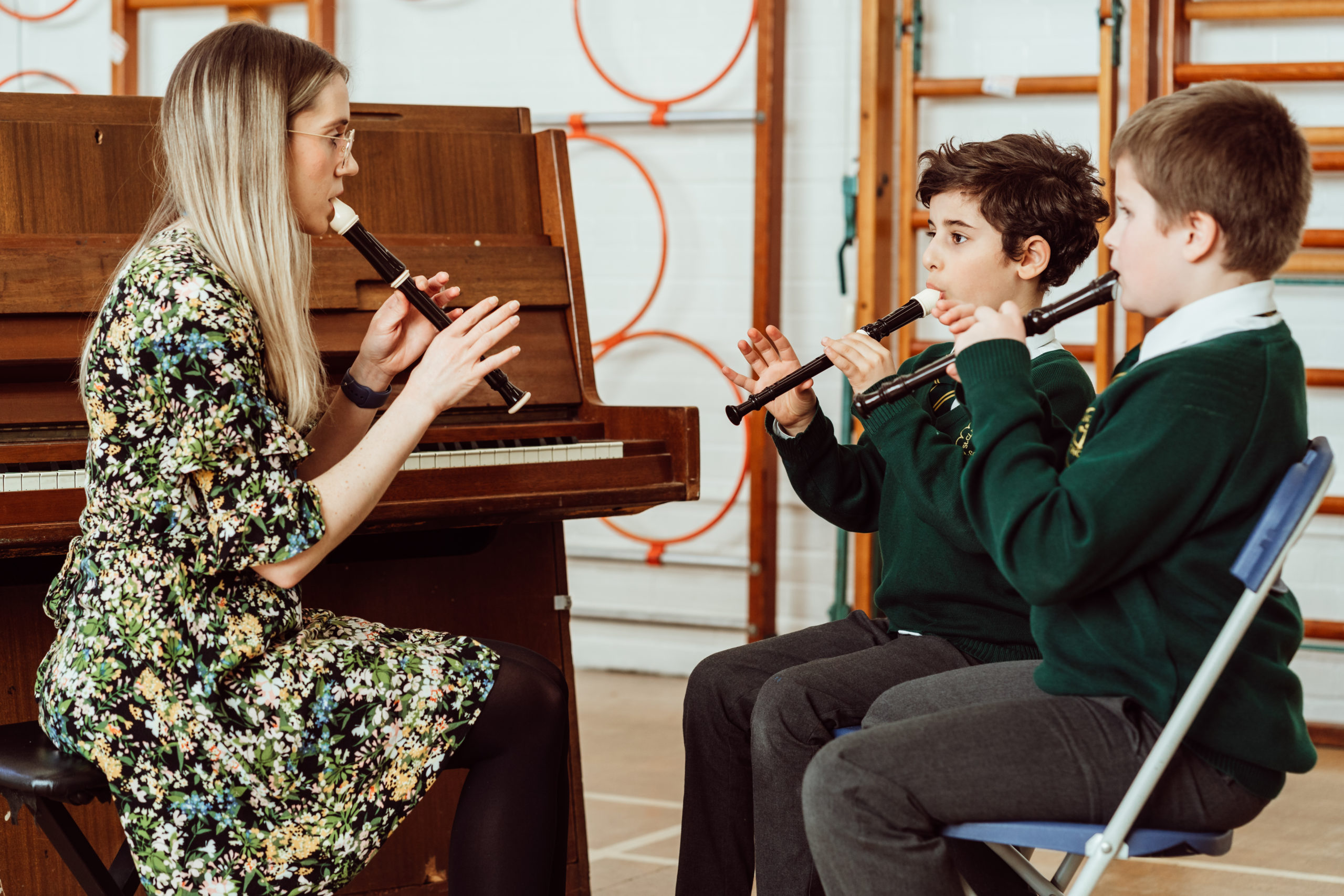 Female sitting in front of KS2 primary pupils, all playing recorders, next to piano, recorders black and white