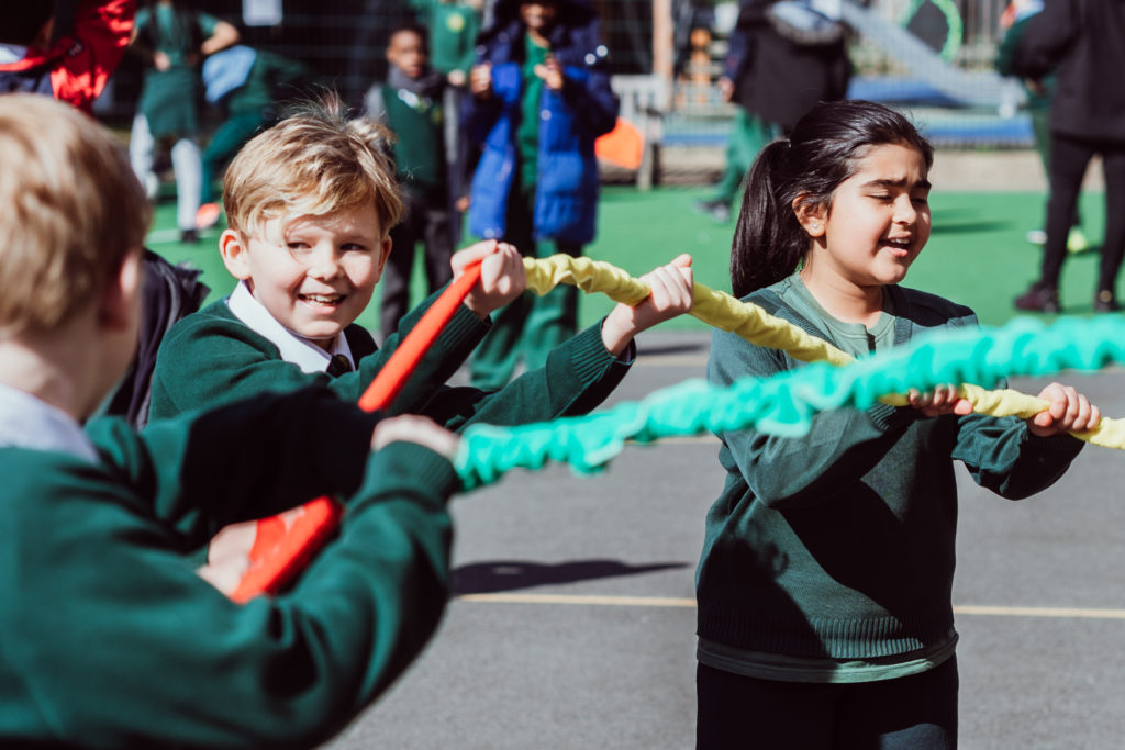 Three KS2 primary pupils holding a red, yellow, green giant scrunchie singing in the playground.