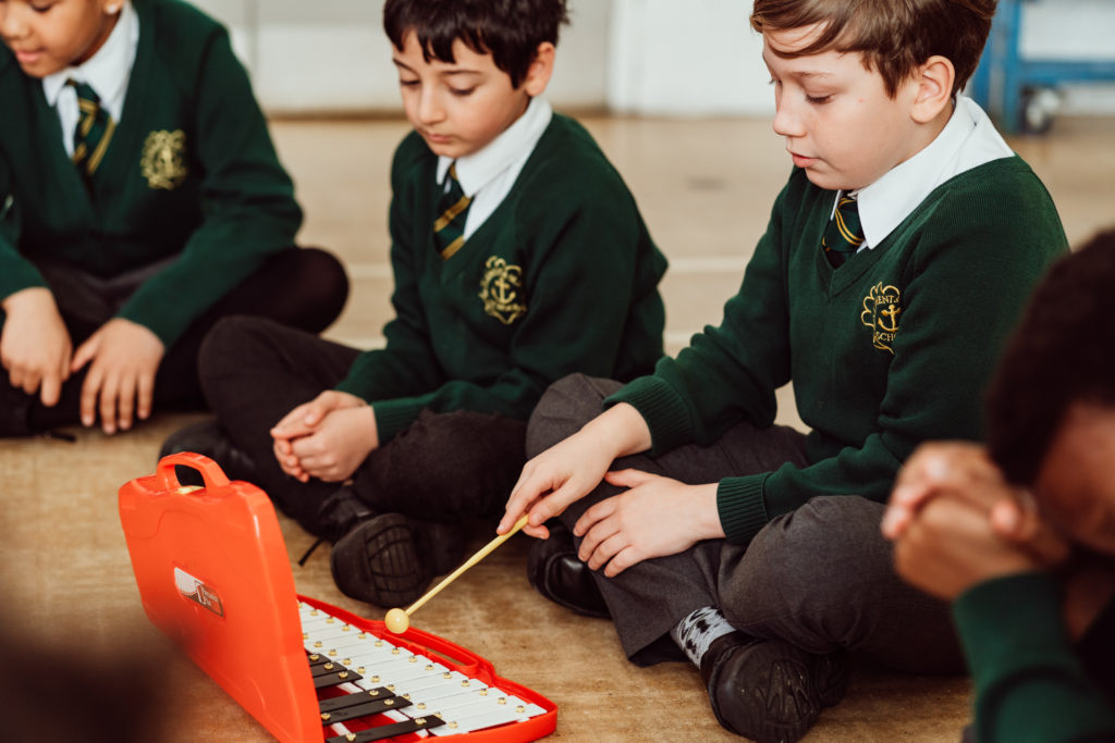 Three KS2 primary pupils sitting on floor of hall, red xylophone in front of them, one pupil holding yellow beater