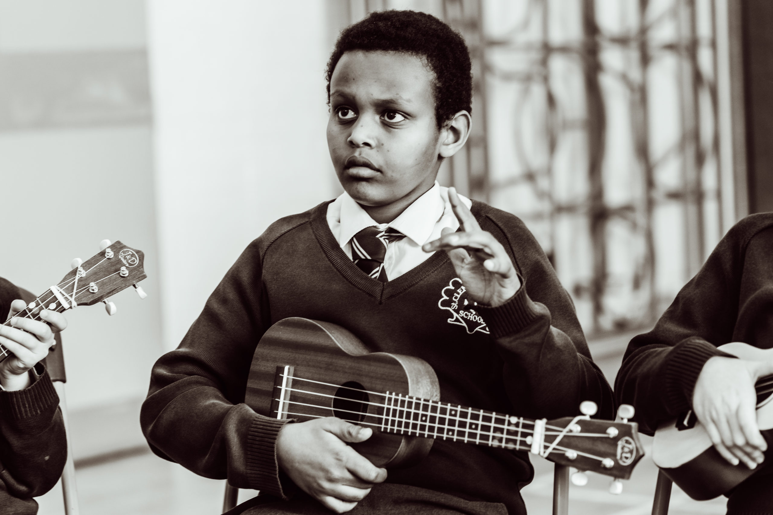 Close up- black and white, KS2 primary pupil, holding ukulele in one hand, holding his other hand up in air
