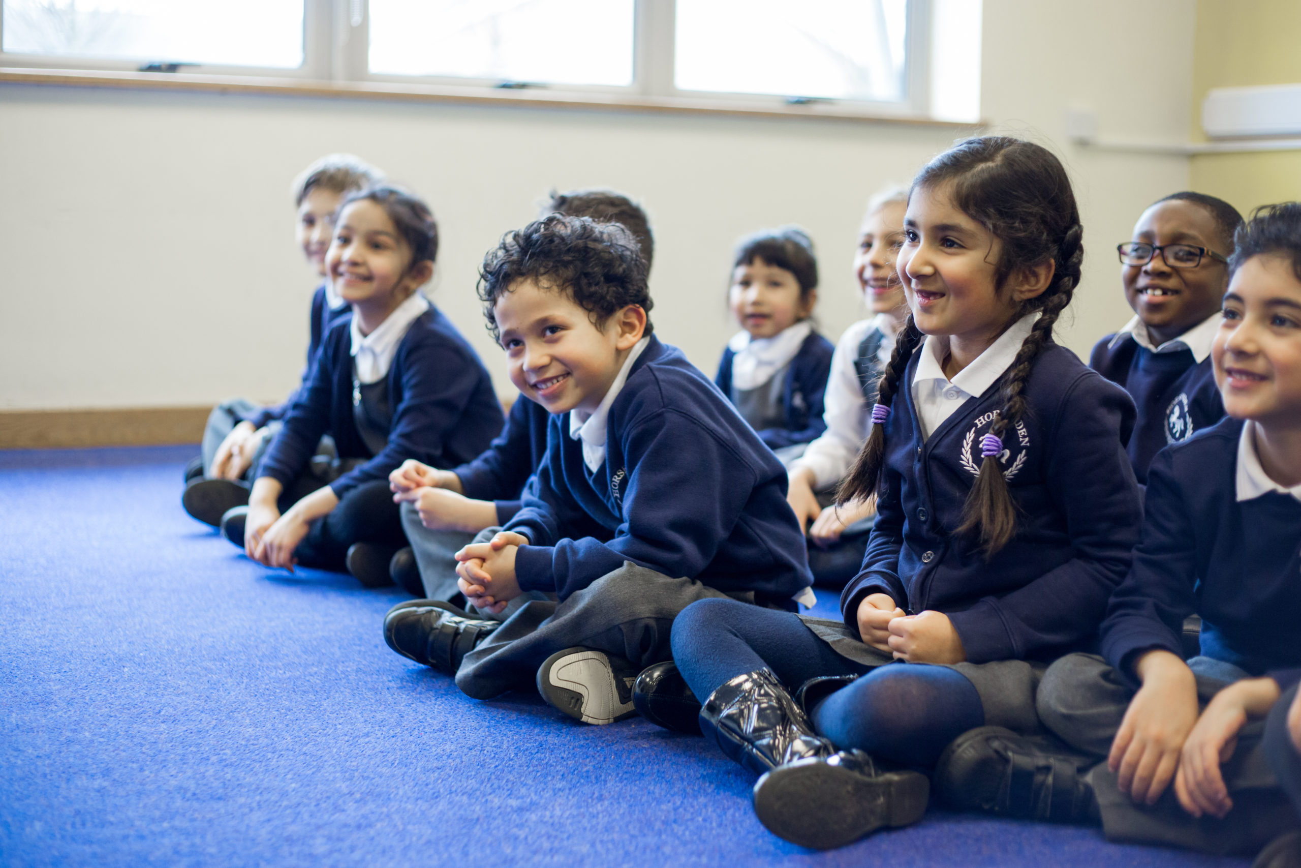Ten KS1 primary pupils sitting on classroom carpet, legs crossed, in lines, smiling, blue and grey uniform, blue carpet