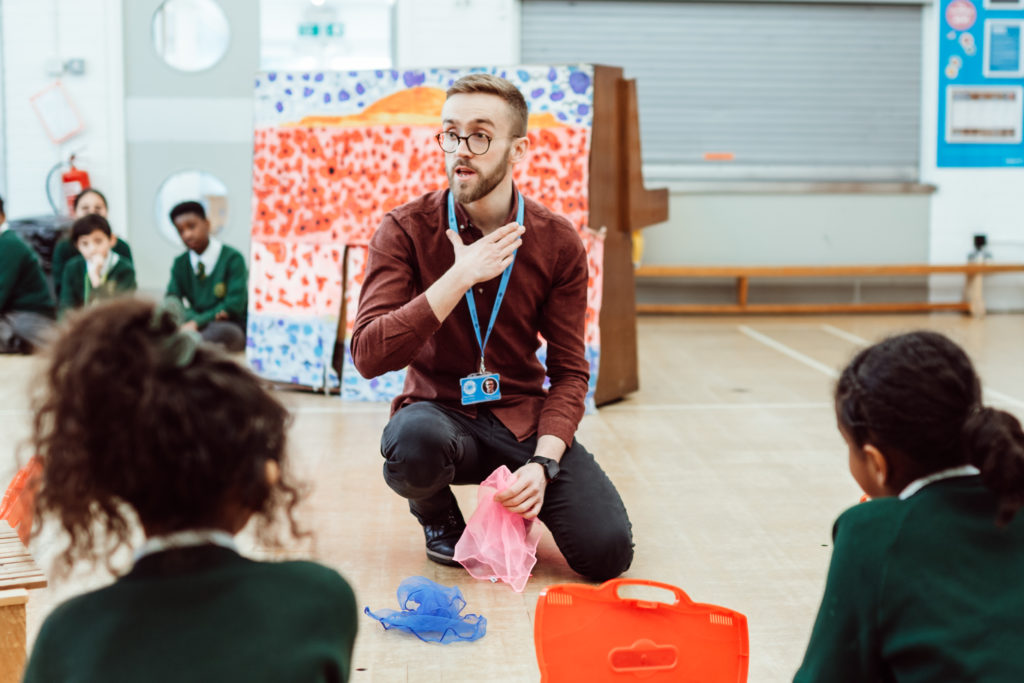 Male kneeling on floor, hand on chest, holding pink scarf. Primary pupils watching in green uniforms, blue scarf on floor.