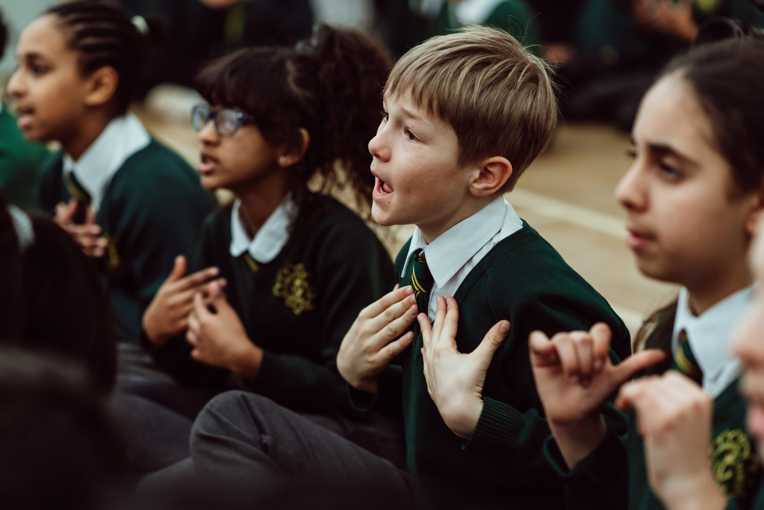 Four KS2 primary children sitting on assembly floor, singing a song. three female pupils and one male, using hand gestures