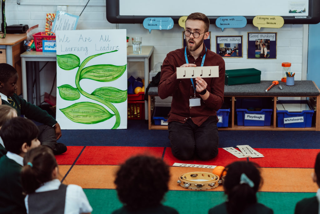Male kneeling on the floor, primary classroom, holding rhythm flashcard in front of KS1 pupils.
