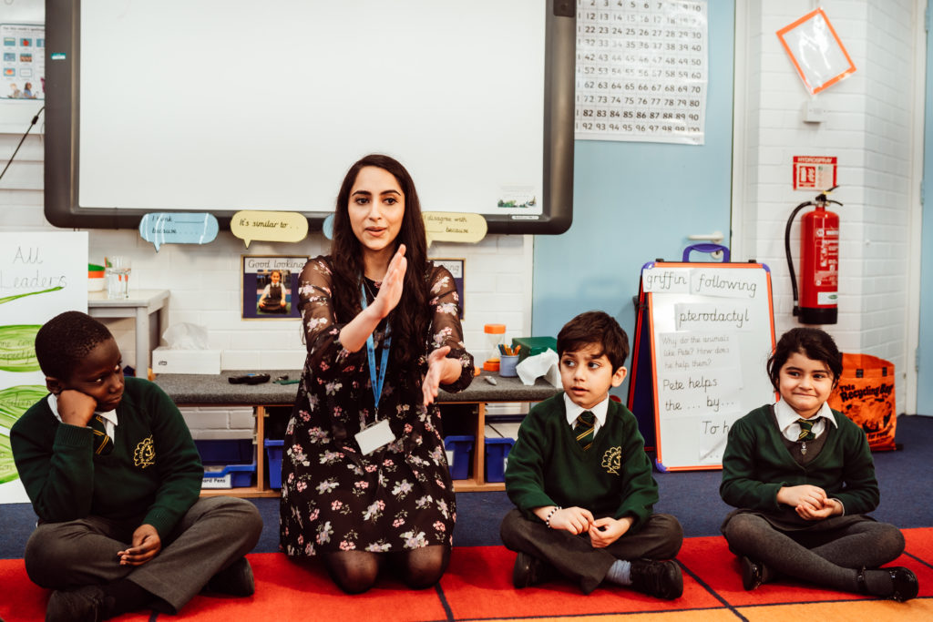 Female sitting on the classroom carpet, next to three KS1 primary pupils, female using hand actions