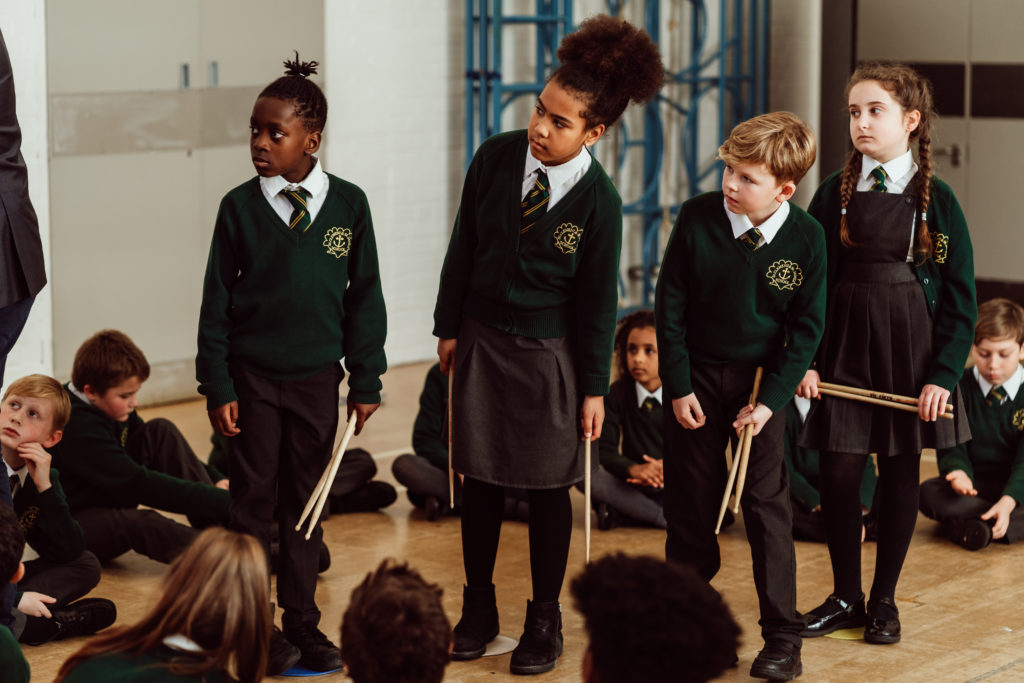 Four pupils standing looking at the board, holding drumsticks, wearing green and grey uniform.