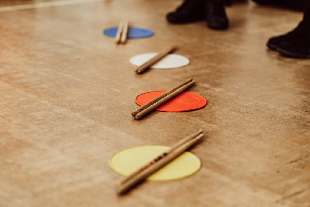 Blue, white, orange and yellow pads on the floor, pair of drumsticks on each pad, drumsticks and floor is brown