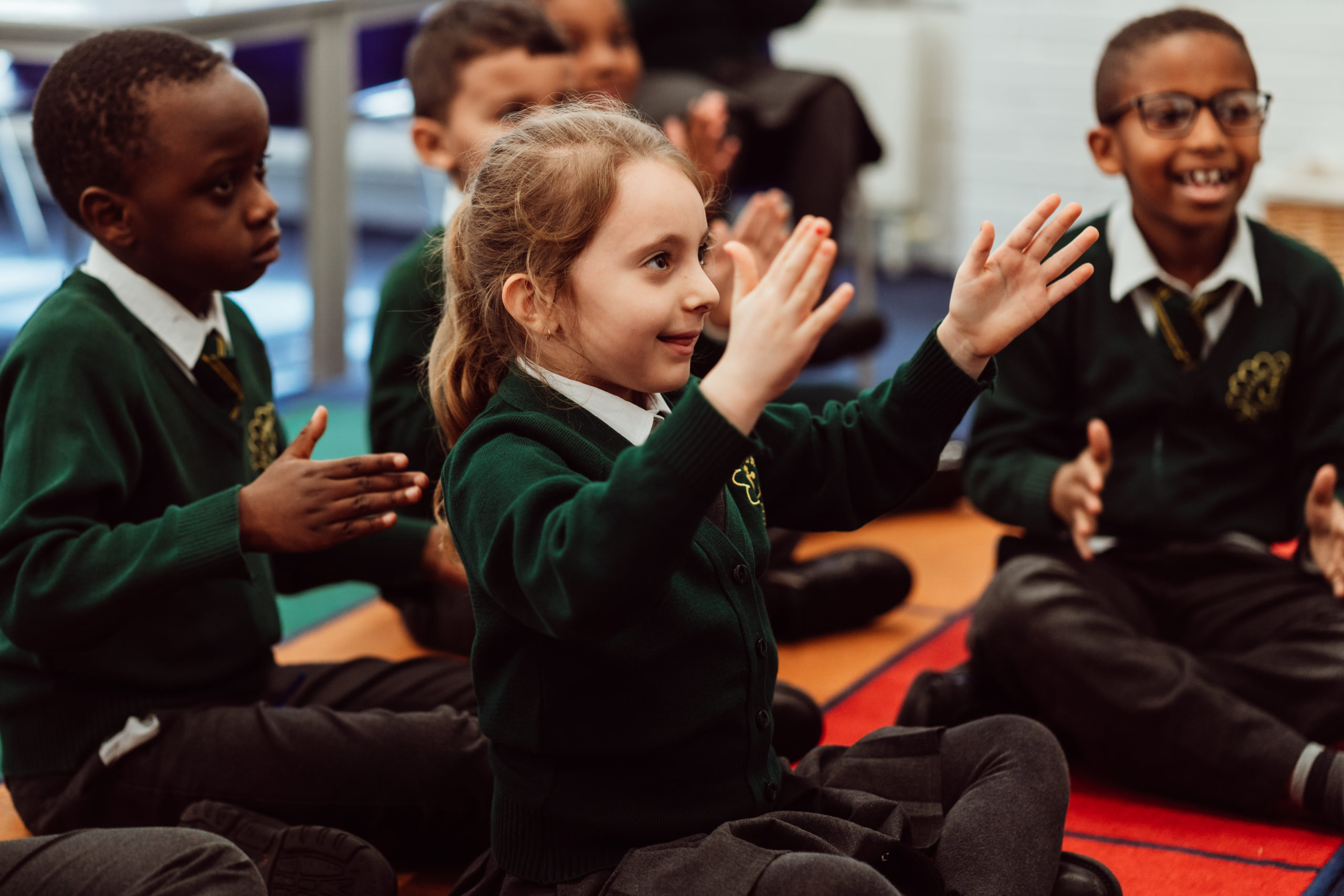Young girl, her hands in the air, smiling about to clap, sitting on the floor in a classroom.