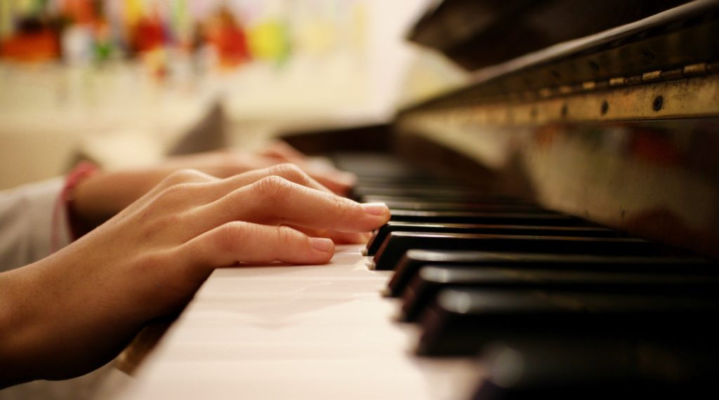 Close up that shows a pair of hands resting on a black and white piano (photographed from the side on).