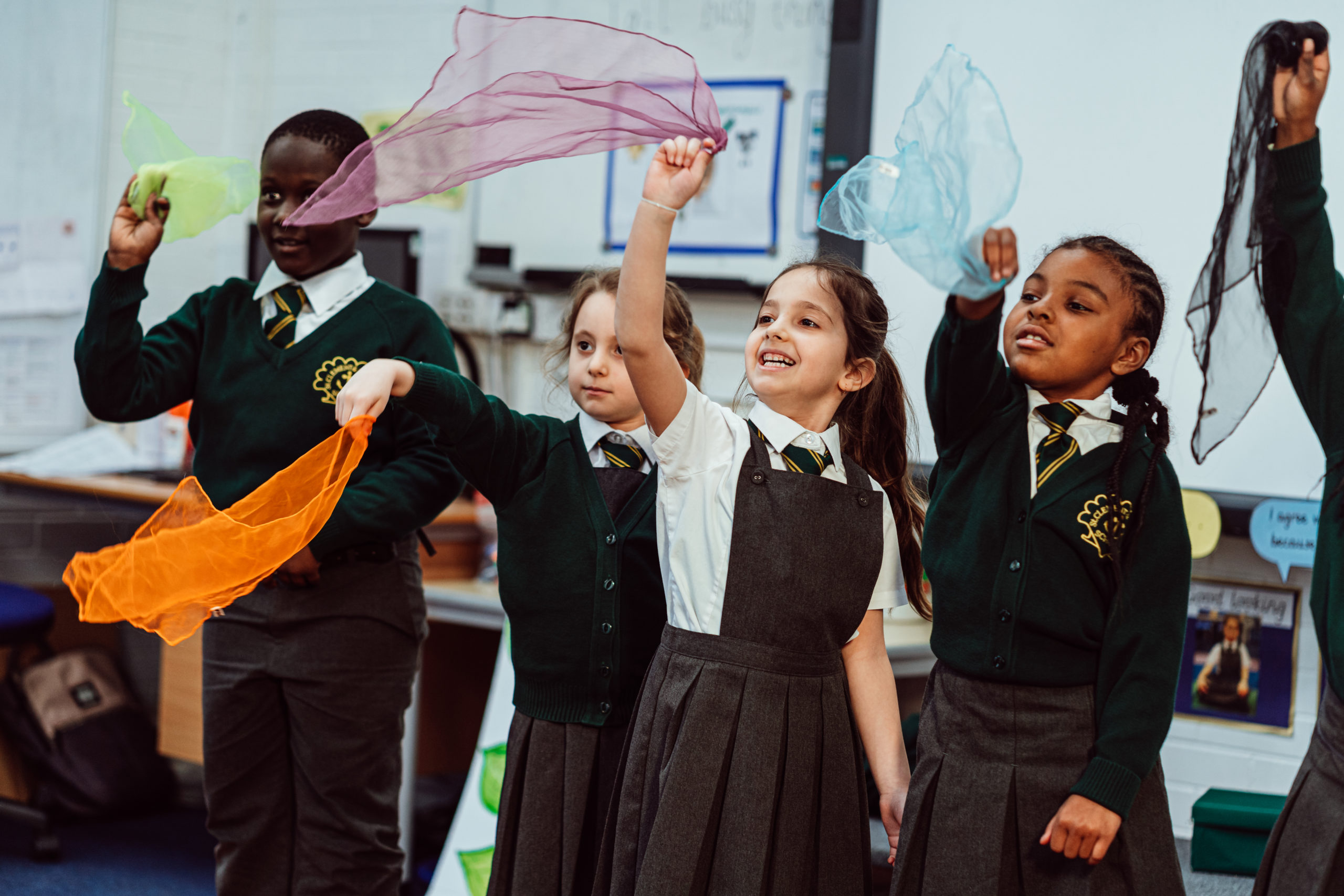 Five KS1 primary pupils, standing, waving a blue, pink, orange, black, yellow scarves in the air, smiling.