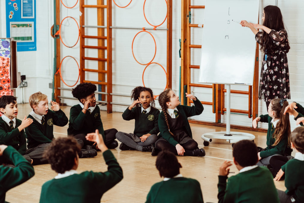 Female at front, pointing at whiteboard with pen, fifteen KS2 primary pupils sitting in circle, signing, using hand actions