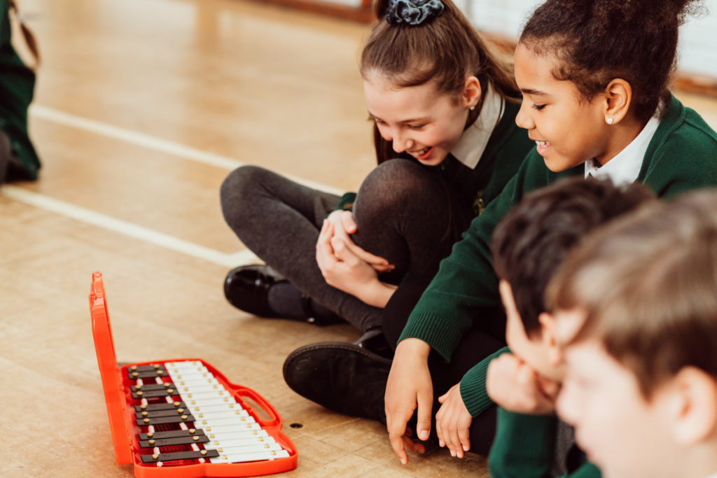 Four primary pupils sitting on floor with glockenspiel in front of them, glockenspiel red, pupils smiling, green and grey uniform