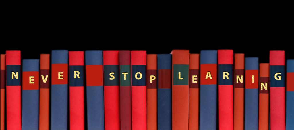 Line of red and blue books, gold writing across saying 'Never Stop Learning', books against a black background.