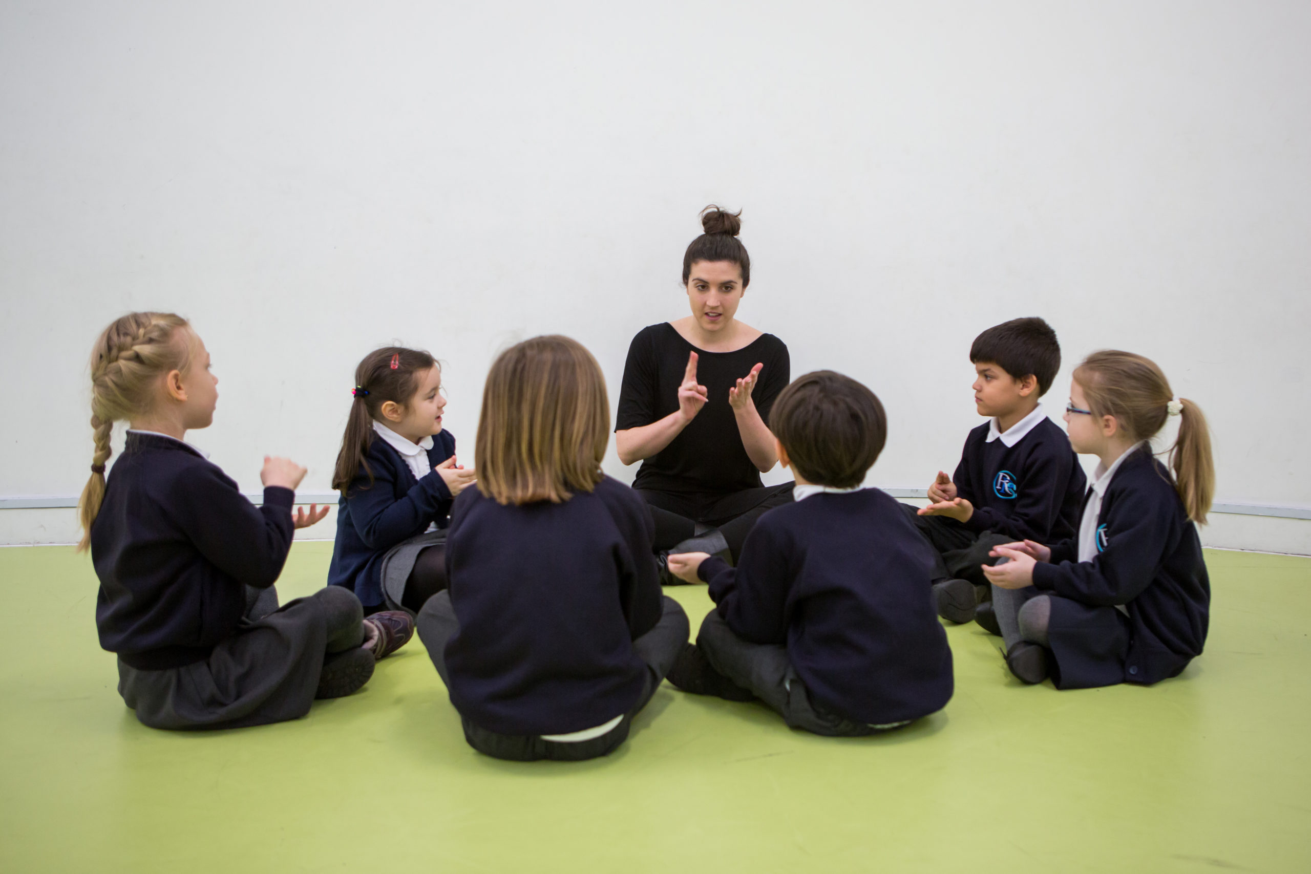 Female sitting on floor, in circle with six KS1 primary pupils, all using both hands for music activity
