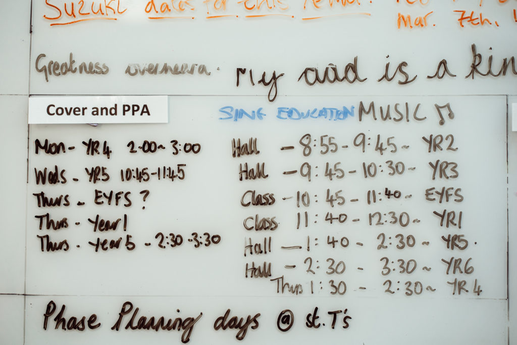 Whiteboard in staffroom that shows Sing Education's primary music timetable for the day along with the cover PPA timetable.