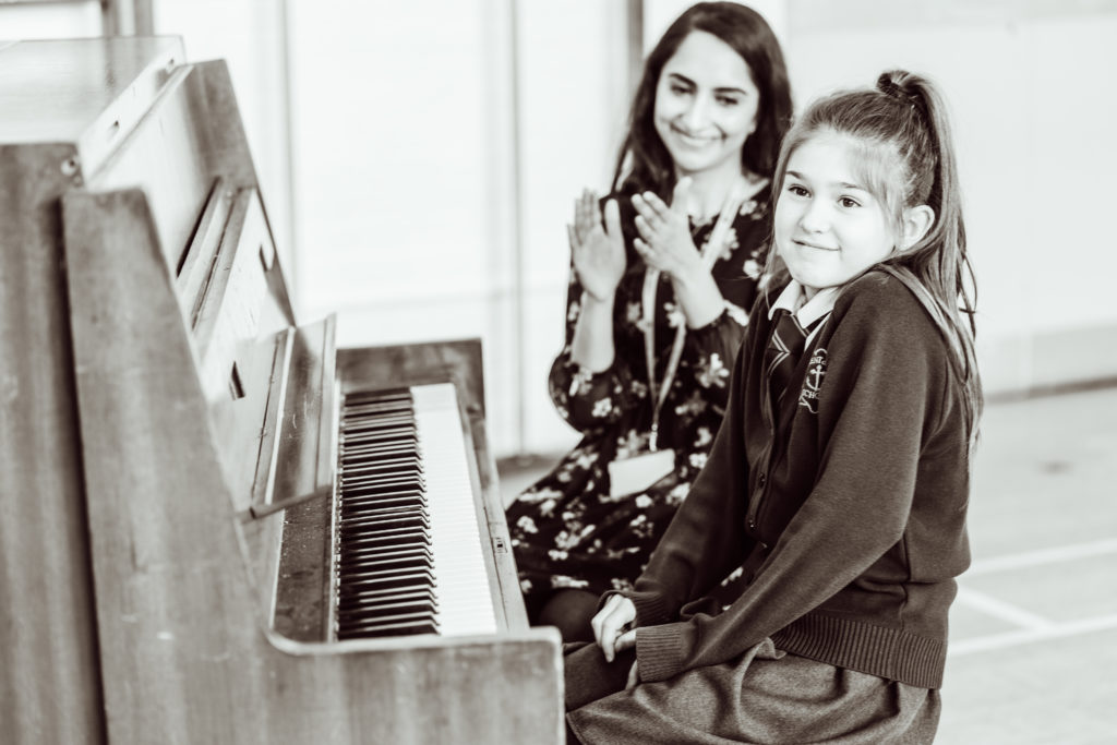 Black and white, female and primary pupil sitting at piano, pupil smiling, shrugging, female holding hands in front of her