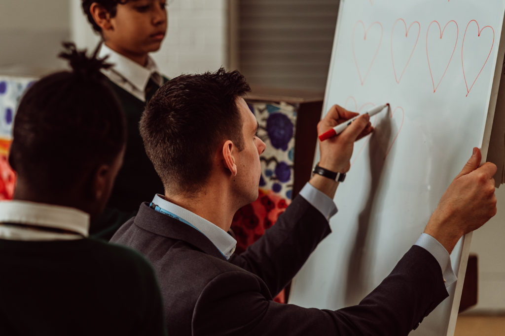 A male kneeling on the floor with two primary pupils either side of him, man drawing hearts on whiteboard