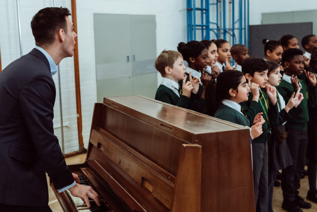 Male playing piano, singing with a choir of primary children, standing in 2 lines, teacher to the left of pupils.