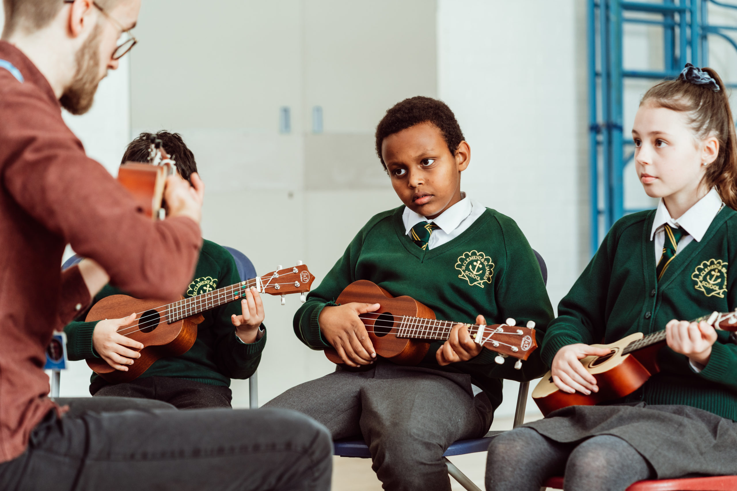 Male and three primary KS2 pupils, all holding ukuleles, all sitting on chairs in the hall.