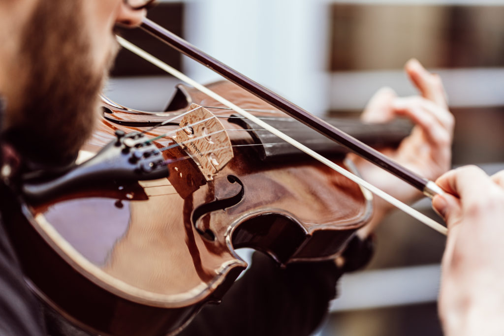 Close up-Male playing violin, violin brown, black neck and tailpiece, male holding brown bow with white hairs