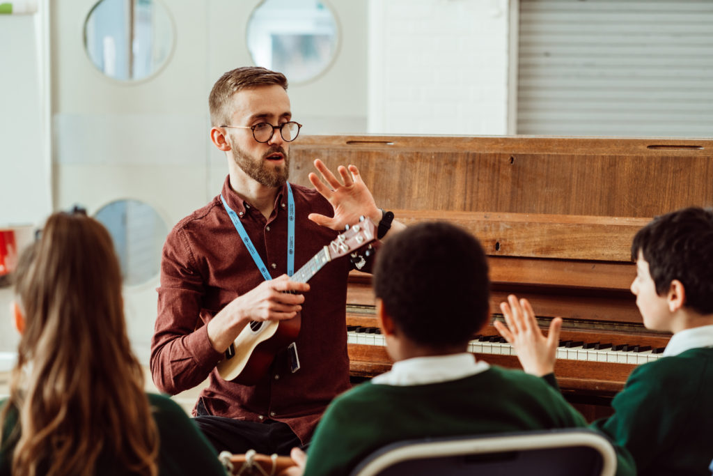 Male sitting on chair, holding ukulele, three primary pupils sitting in front, only see the backs of pupils heads.