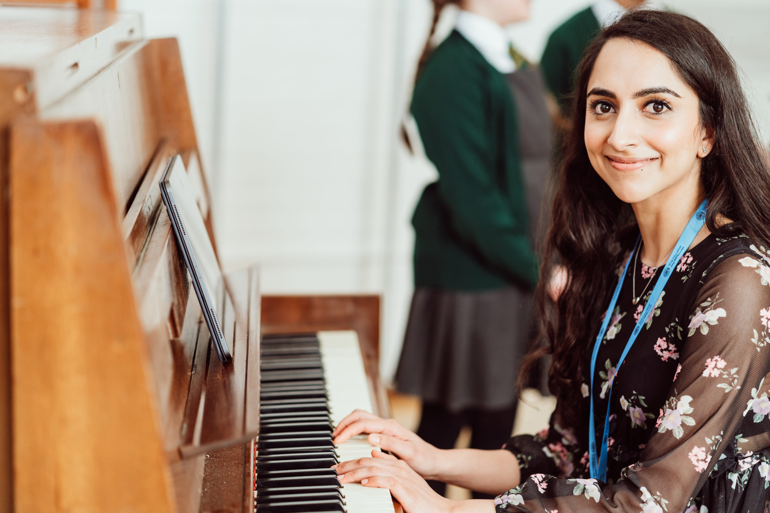 Female sitting at a piano, hands on the piano, female in black floral dress, two primary pupils in background.