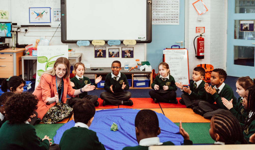 Female sitting in a circle on floor with fifteen KS1 children clapping, blue pond prop, soft frog prop on floor.