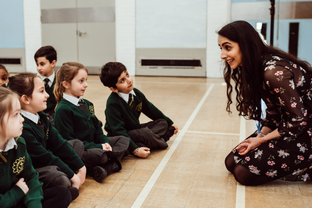 Female kneeling on the floor in front of six primary pupils, pupils are looking at the female, in green uniforms.