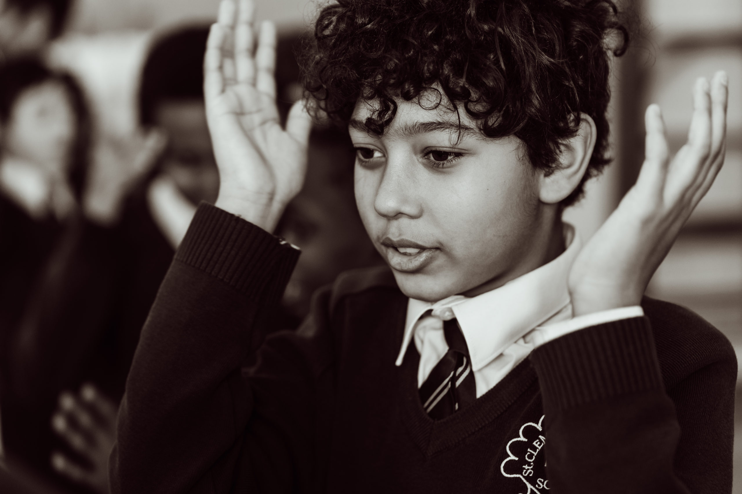 Close up, black and white, KS2 primary pupil, boy, holding hands up to the sides of his head, mouth open.