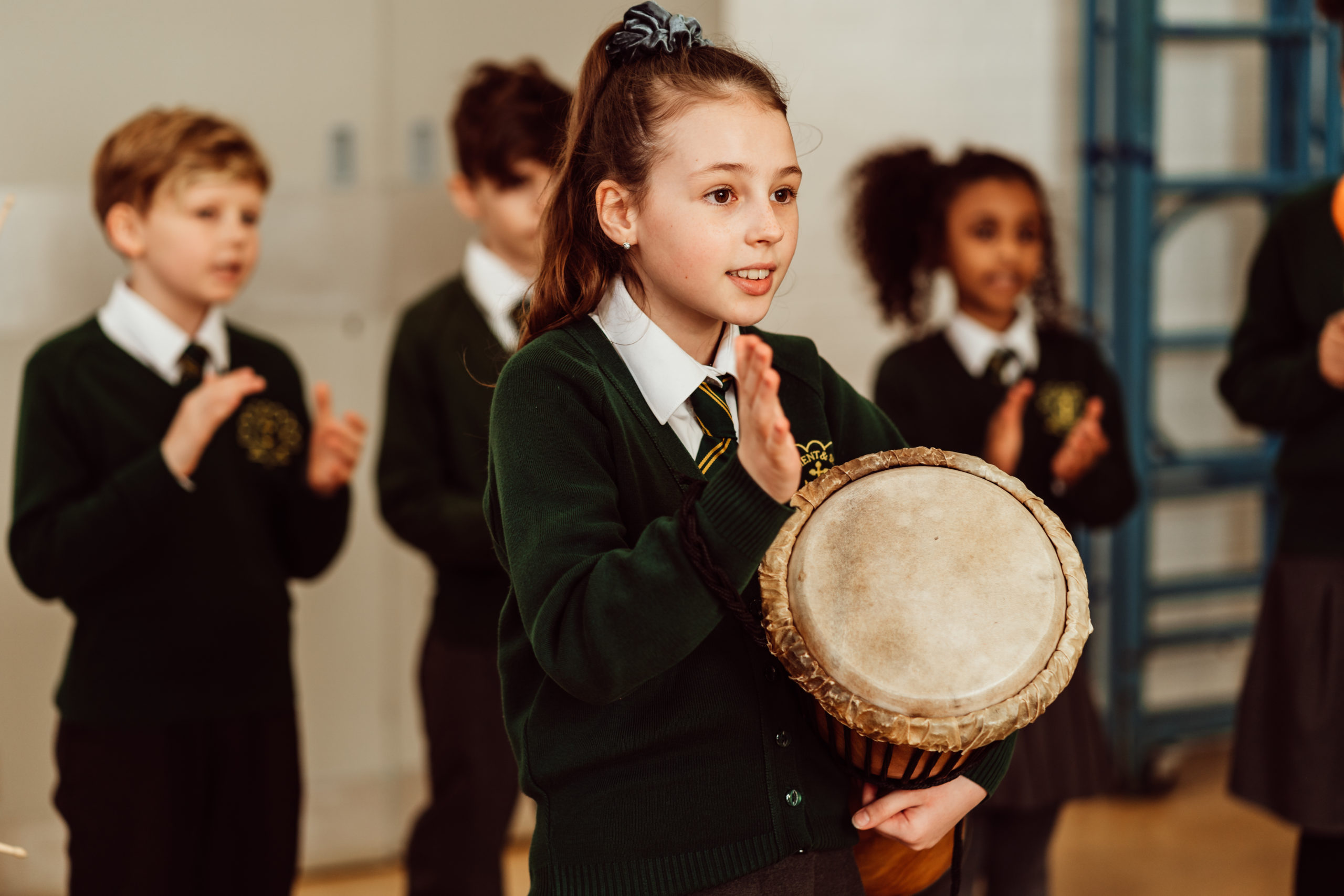 Primary pupil, girl, holding drum in one hand, other hand raised above the drum, three primary pupils in the background.