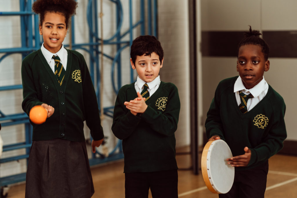 Three primary pupils standing in a line,two clapping, one holding a maraca, another primary pupil standing to the left.
