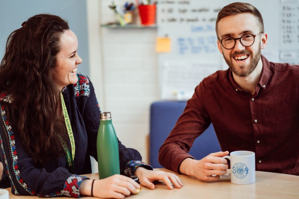 A woman and a man talking and smiling in a school staff room.