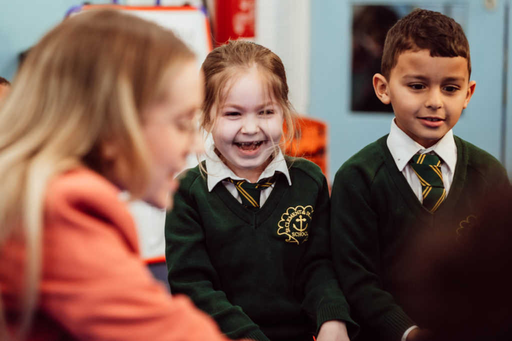 Close up, two KS1 primary pupils, girl and a boy (left to right), both smiling, female head blurred, in foreground.