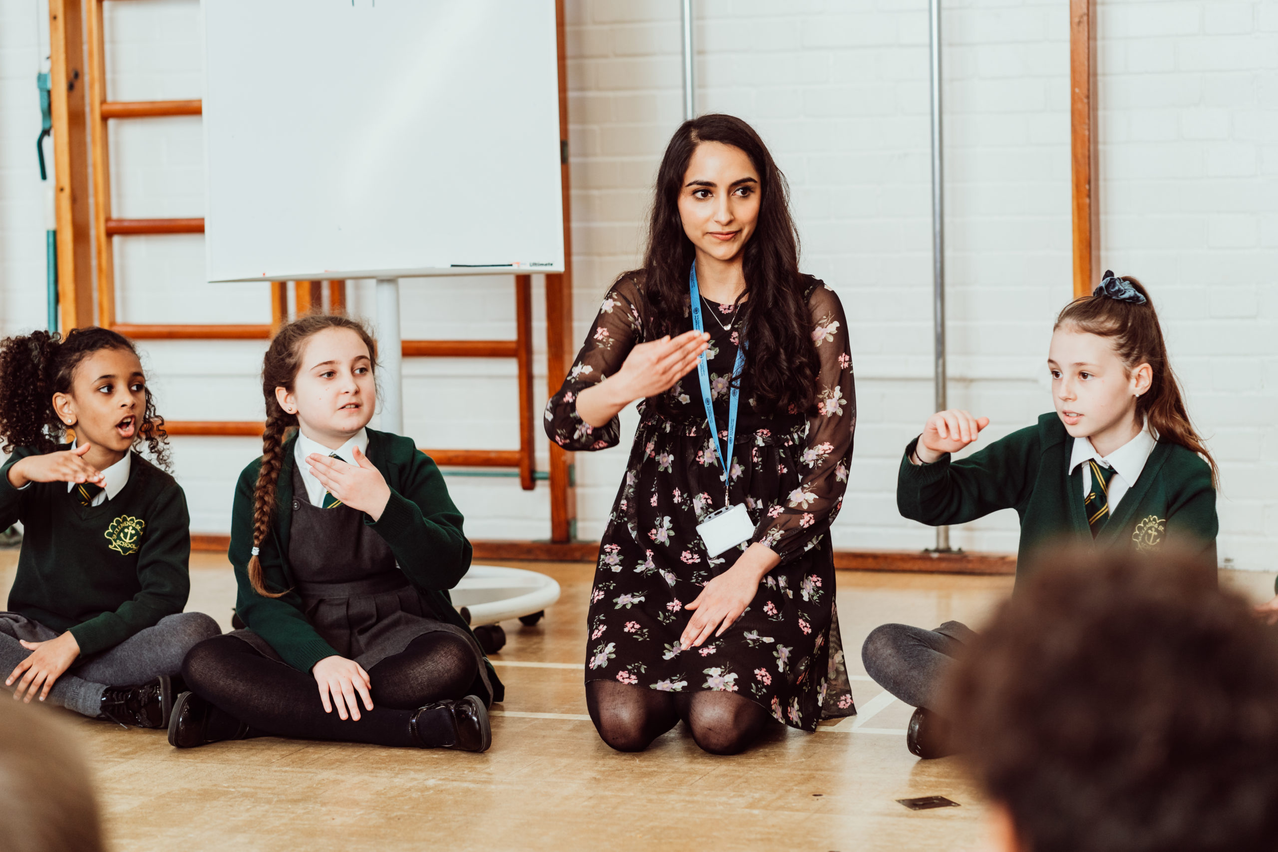 Female kneeling on the floor with hand out in front of her, three primary pupils sitting next to her copying.