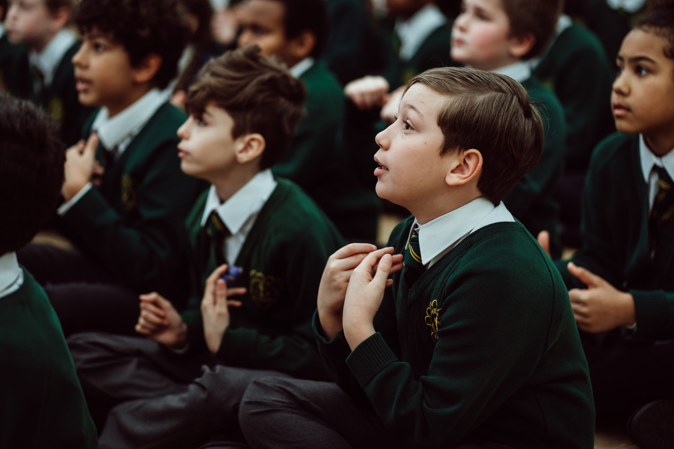 Primary pupil, boy sitting on the floor, holding hands up to his chest, looking forward, six pupils in the background.