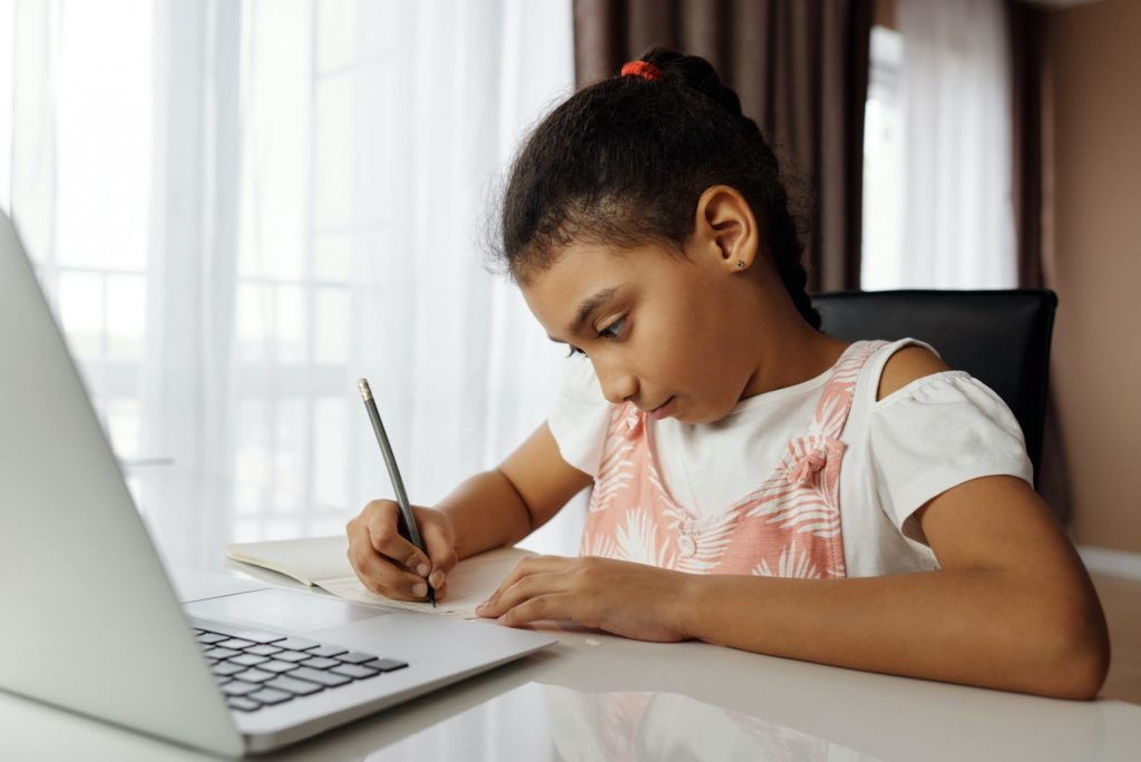 Primary school pupil sitting at a laptop with pencil in hand. The girl is doing sat infant of a window, doing homework.