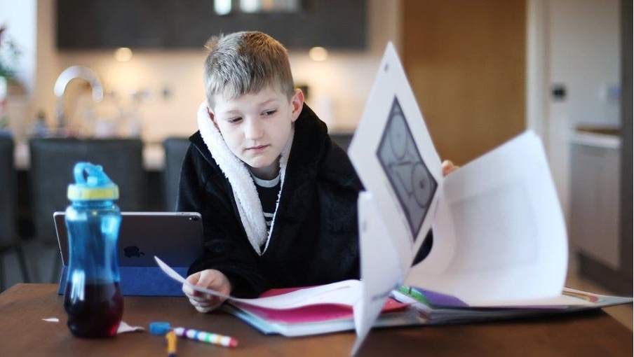 A young boy sat looking through homework papers. He has a pencil in his hand and is wearing a dressing gown.