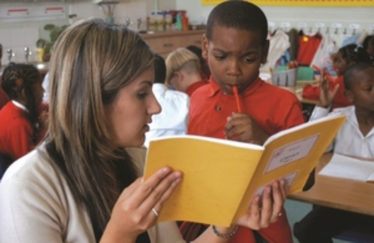 Teacher is helping a small child with a problem in his exercise book. The child has a puzzled expression