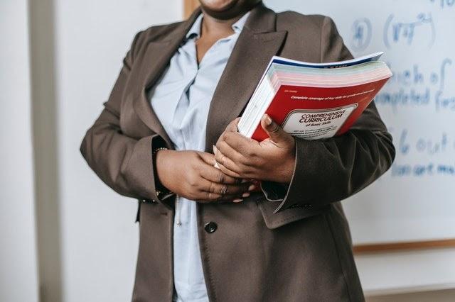 Female Headteacher in a blazer holding a stack of books