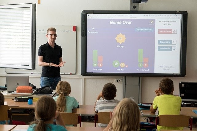 A teacher is playing an educational game with his class of primary school children