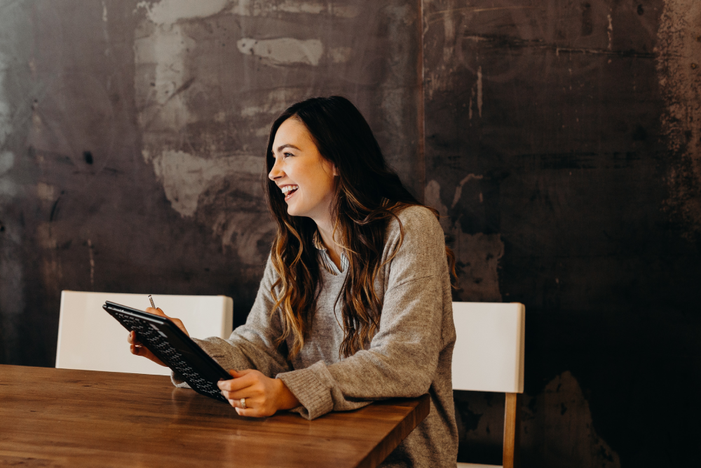 Smiling woman sitting at a desk with her ipad