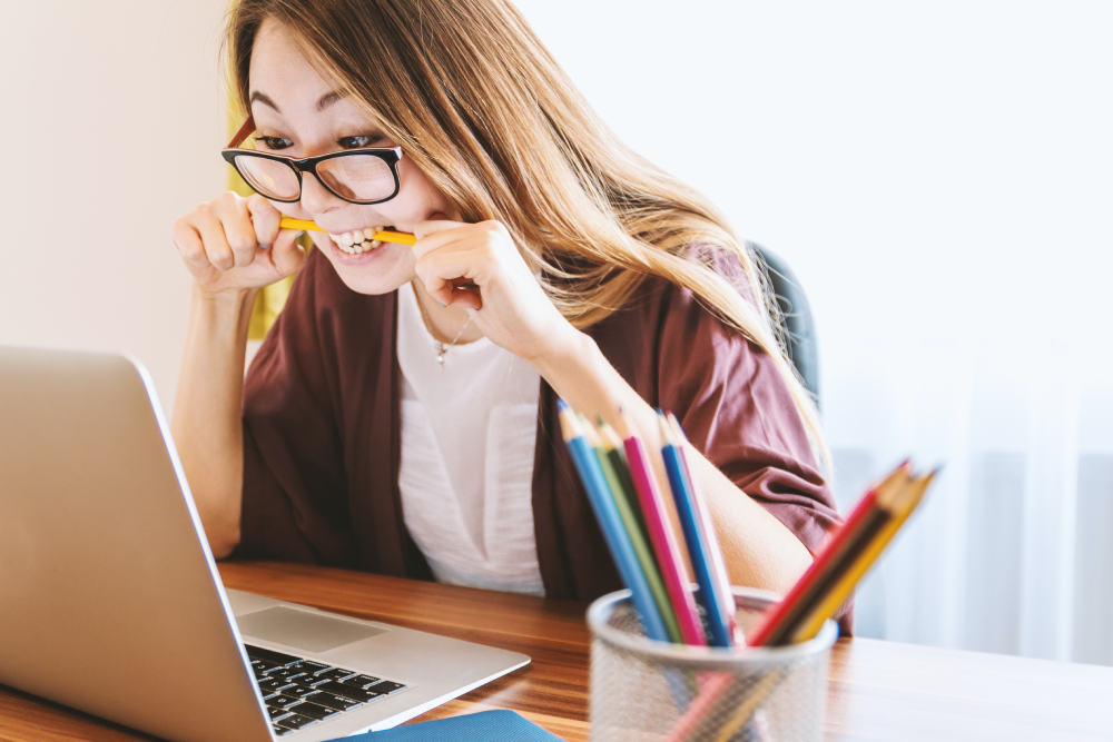 Woman biting a pencil whil sitting in front of her laptop
